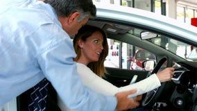 Mujer que hecha una ojeada un nuevo coche almacen de video