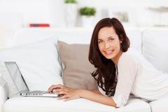 Mujer que hojea en el ordenador portátil Imagenes de archivo