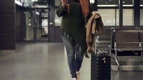 Mujer que hojea en línea en smartphone en aeropuerto de la noche