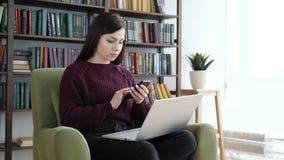 Mujer que hojea en Smartphone mientras que se sienta en el sofá en oficina metrajes