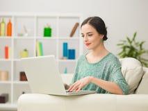 Mujer que hojea Internet en el ordenador portátil Imagen de archivo libre de regalías