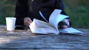 Mujer que hojea a través de un libro de tapa dura grande almacen de metraje de vídeo