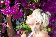 Mujer que huele las flores rosadas Fotos de archivo