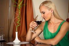 Mujer que huele un vino en un vidrio Imagenes de archivo