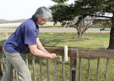 Mujer que impermeabiliza su cubierta del patio Foto de archivo libre de regalías