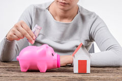 Mujer que inserta el dinero en una hucha y un hogar modelo Fotos de archivo