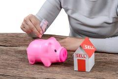 Mujer que inserta el dinero en una hucha y un hogar modelo Fotos de archivo libres de regalías
