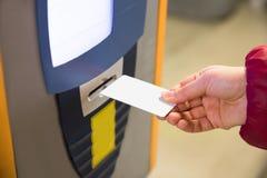 Mujer que inserta la multa de aparcamiento en la máquina Imágenes de archivo libres de regalías