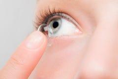 Mujer que inserta una lente de contacto en ojo imagen de archivo