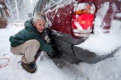 Mujer que instala encadenamientos de neumático imagen de archivo libre de regalías