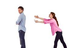 Mujer que intenta abrazar al hombre Fotos de archivo