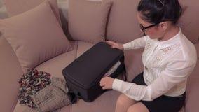 Mujer que intenta caber toda la ropa en maleta almacen de metraje de vídeo