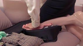 Mujer que intenta cerrar cierre de la maleta del desbordamiento para arriba metrajes