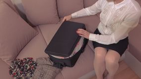 Mujer que intenta cerrar la maleta metrajes