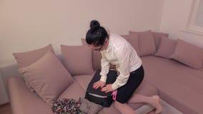 Mujer que intenta cerrar la maleta del desbordamiento en el sofá metrajes
