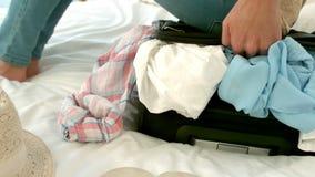 Mujer que intenta cerrar su maleta llena almacen de video