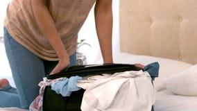 Mujer que intenta cerrar su maleta llena metrajes