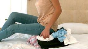 Mujer que intenta cerrar su maleta llena almacen de metraje de vídeo