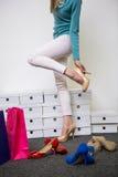 Mujer que intenta en diversos zapatos imagen de archivo libre de regalías