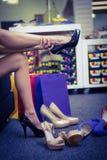 Mujer que intenta en diversos zapatos imagenes de archivo