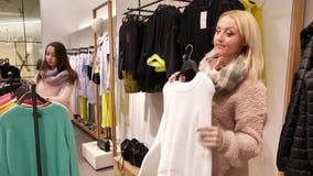 Mujer que intenta en el suéter blanco en tienda almacen de metraje de vídeo