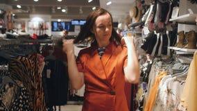 Mujer que intenta en el vestido en tienda de ropa almacen de metraje de vídeo