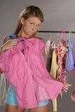 Mujer que intenta en la ropa Fotos de archivo