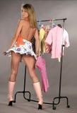 Mujer que intenta en la ropa Imagenes de archivo