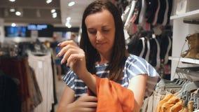 Mujer que intenta en la ropa en una tienda de ropa La mujer elige la ropa en la tienda almacen de video