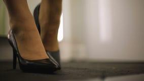 Mujer que intenta en los zapatos de cuero hermosos con los talones, opinión del primer de pies femeninos metrajes