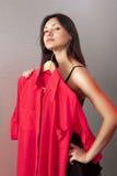 Mujer que intenta encendido la camisa roja en departamento Fotos de archivo