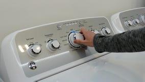 Mujer que intenta la nueva lavadora en el dispositivo de GE de la exhibición almacen de video