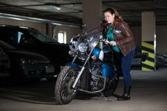 Mujer que intenta sentarse en la motocicleta, colocándose en el aparcamiento oscuro foto de archivo libre de regalías