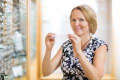 Mujer que intenta sobre los vidrios en el óptico Store fotografía de archivo libre de regalías