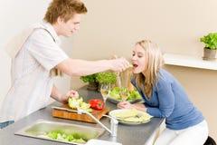 Mujer que introduce del hombre de la ensalada del cocinero de los pares del almuerzo Foto de archivo