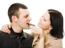 Mujer que introduce un chocolate del hombre. Foto de archivo libre de regalías