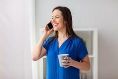 Mujer que invita a smartphone en la oficina o el hogar Foto de archivo libre de regalías