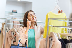 Mujer que invita a smartphone en la tienda de ropa Imágenes de archivo libres de regalías