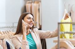 Mujer que invita a smartphone en la tienda de ropa Foto de archivo