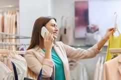 Mujer que invita a smartphone en la tienda de ropa Fotografía de archivo libre de regalías