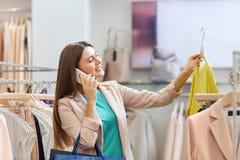 Mujer que invita a smartphone en la tienda de ropa Imagen de archivo libre de regalías