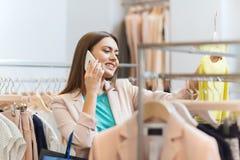 Mujer que invita a smartphone en la tienda de ropa Fotos de archivo libres de regalías