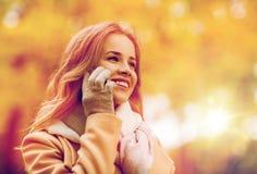 Mujer que invita a smartphone en parque del otoño Fotos de archivo libres de regalías