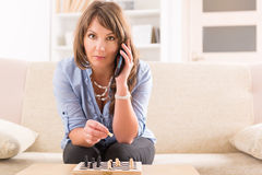 Mujer que juega a ajedrez en casa fotografía de archivo libre de regalías