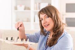 Mujer que juega a ajedrez en casa foto de archivo