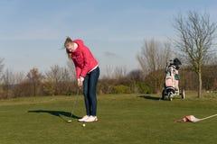 Mujer que juega al golf que se alinea un putt Fotos de archivo