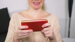Mujer que juega al juego en el teléfono elegante almacen de video