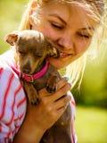 Mujer que juega con el pequeño perro afuera imagen de archivo libre de regalías