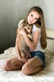 mujer que juega con el pequeño perro que se sienta en cama Imagenes de archivo