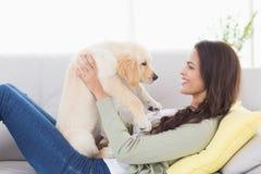 Mujer que juega con el perrito en el sofá foto de archivo